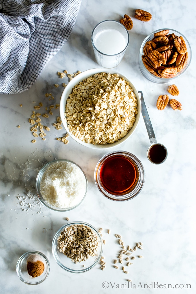 Ingredients for maple pecan granola including oats, maple syrup, pecans, coconut, and sunflower seeds.