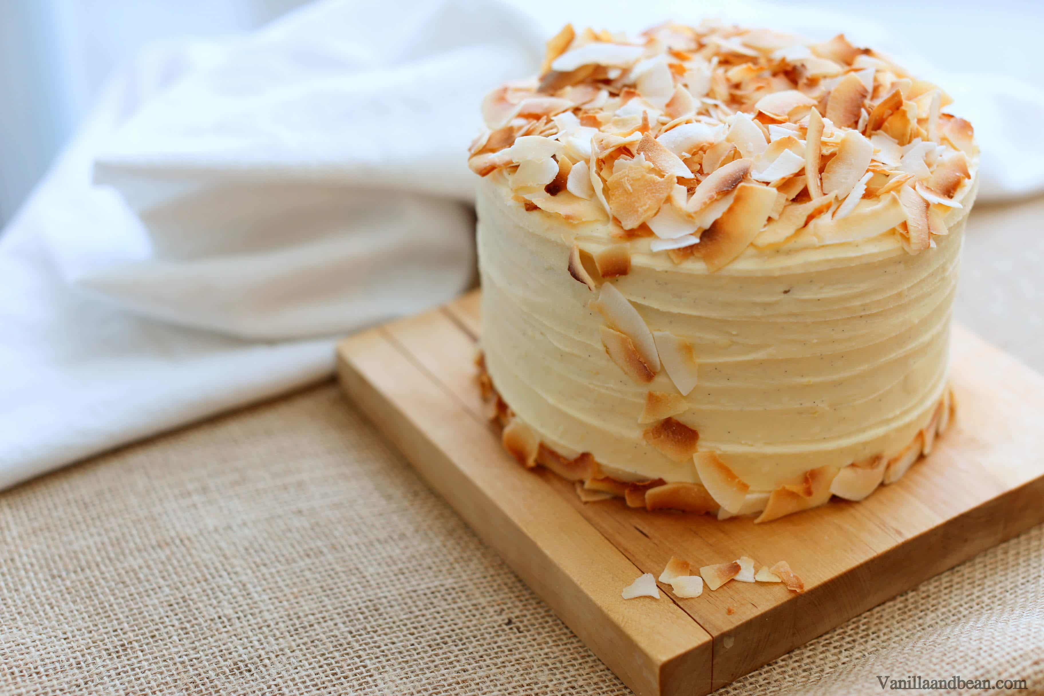 Hummingbird Cake topped with coconut flakes setting on a cake board.
