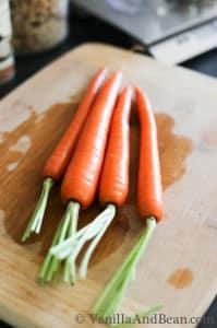 Four medium carrots on a chopping board.