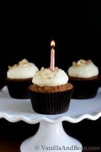 Three carrot cupcakes with icing on a cake stand. The middle cupcake has a small candle lit.