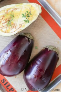 Whole and sliced eggplants in a tray.