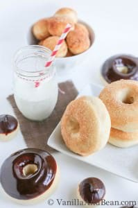 Baked doughnuts topped with ganache on a plate and doughnut holes in a small bowl