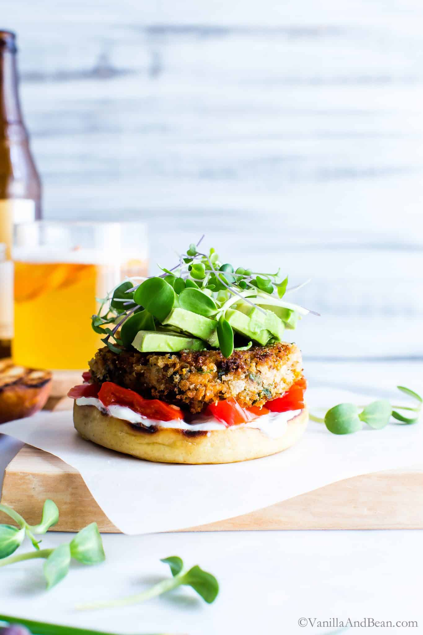 Sweet Potato Burger topped with avocado and sprouts, setting on a cutting board ready to eat.