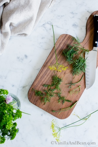 Fresh dill on a cutting board with a knife.
