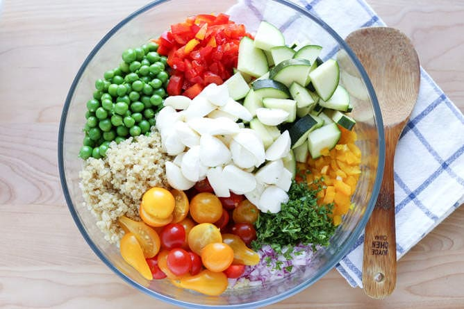 Chopped and diced salad ingredients in a large glass bowl.
