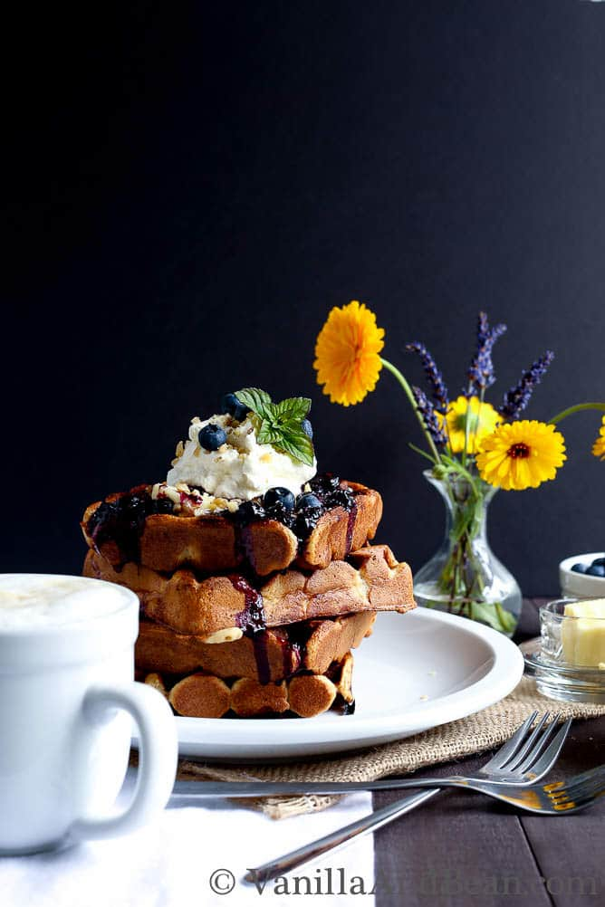 Layers of waffles topped with blueberry, syrup, cream and walnuts.