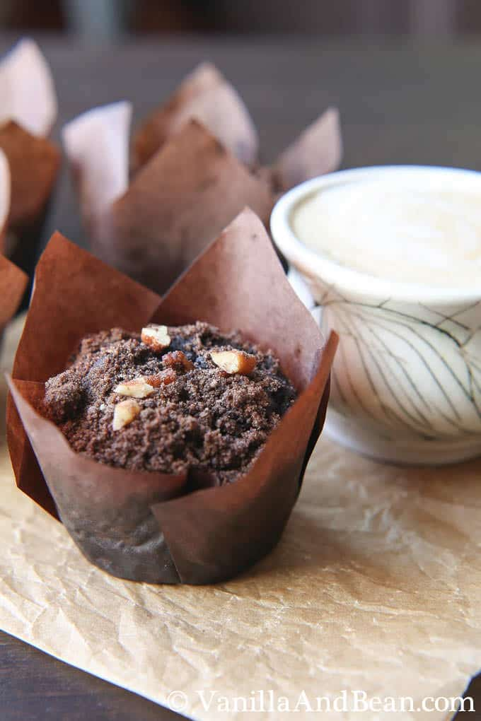 A chocolate muffin with crumbly topping with a cup of milk