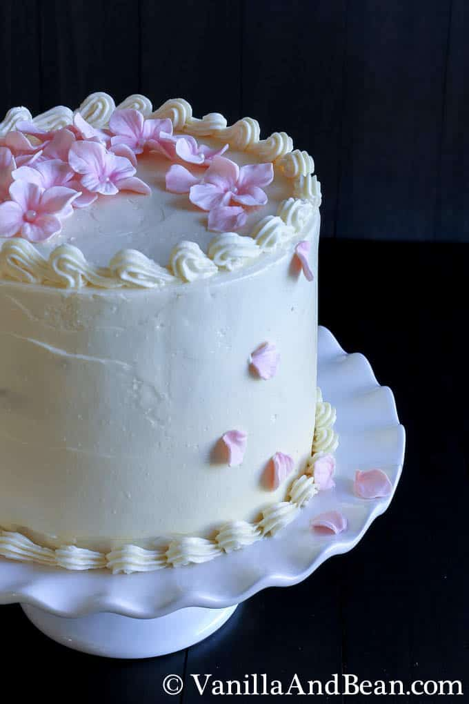 A fully-decorated decorated cake embellished with flowers on top and a few petals on one side