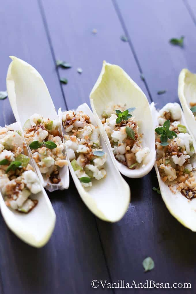 Endive leaves each with pear and blue cheese mixture topped with walnuts