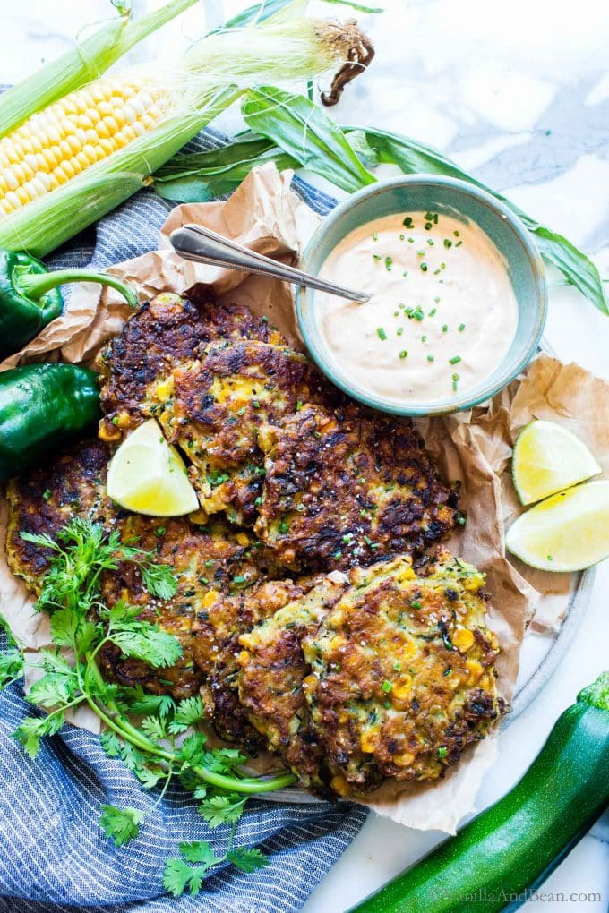 Overhead shot of Corn Zucchini Fritter with Chipotle Cream on a serving platter.