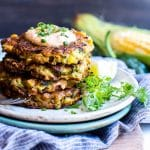 Corn and Zucchini Fritters stacked tall on a plate.