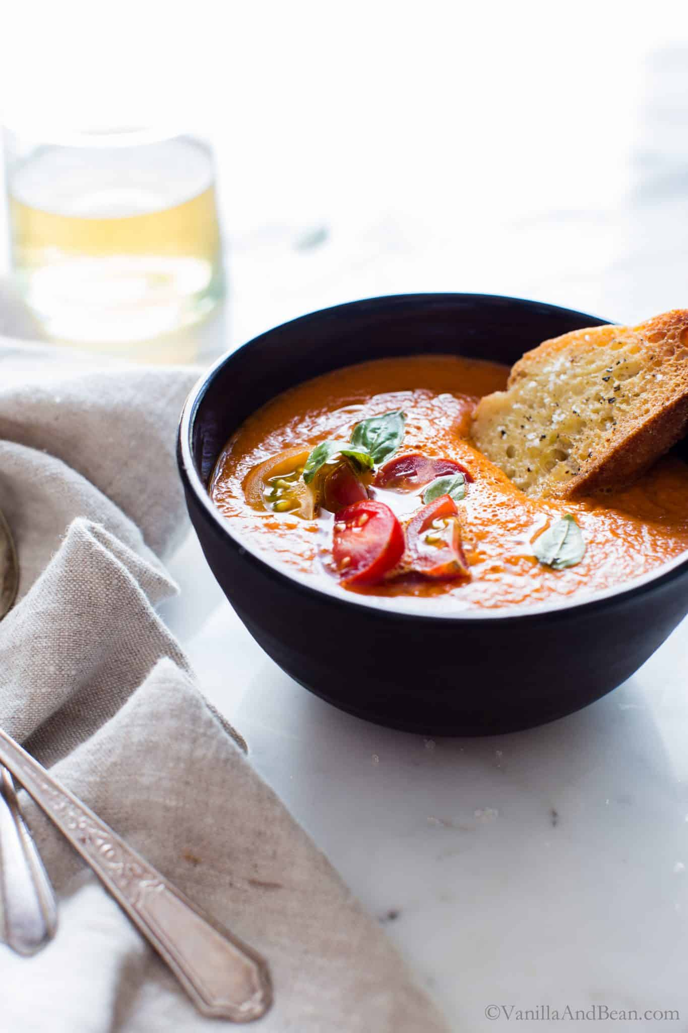 Roasted Red Bell Pepper and Heirloom Tomato Soup in a bowl with a slice of bread ready for sharing.