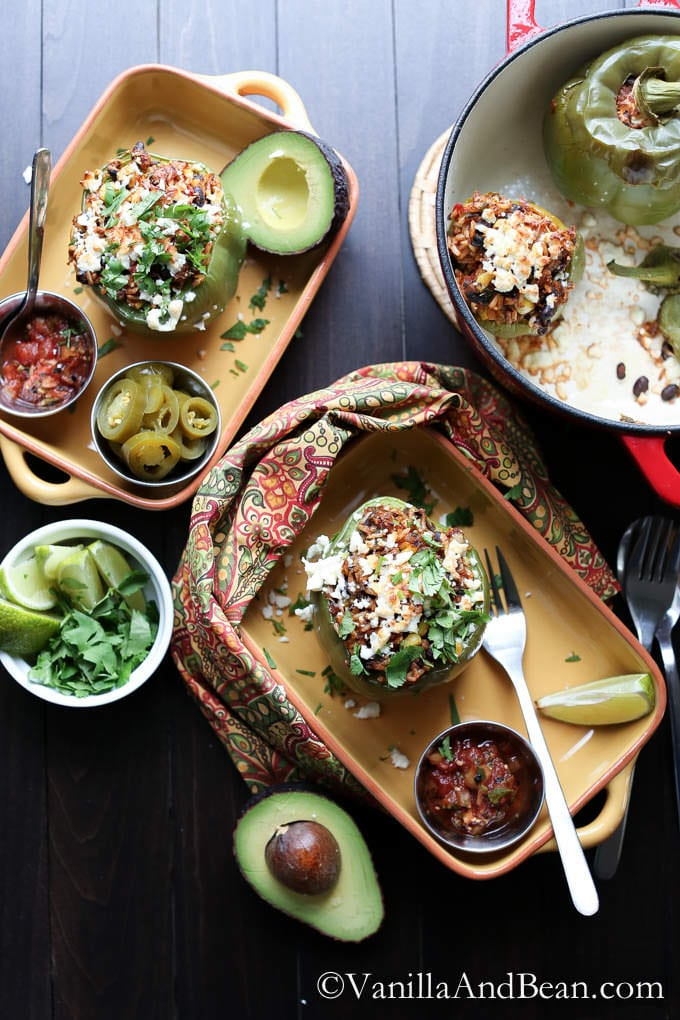 Roasted stuffed peppers, salsa and slices of avocado served in casserole dishes