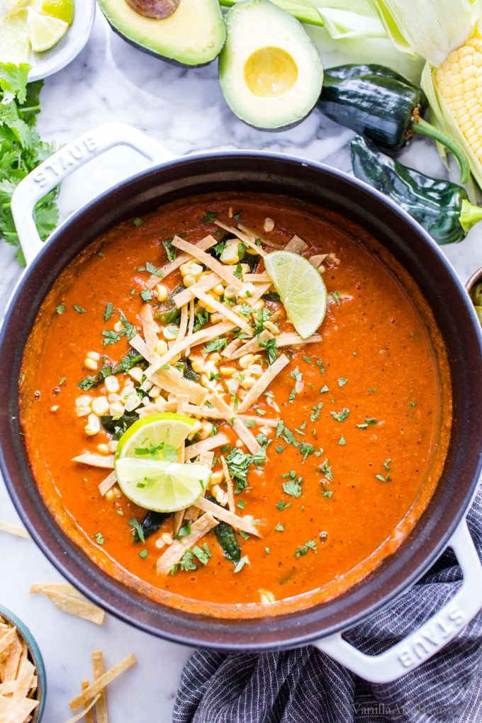 A Dutch oven full of of healthy vegan tortilla soup garnished with lime wedges, avocados and tortilla strips.