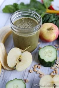 Chocolate Green Super Smoothie on a small mason jar surrounded by sliced fruits, chard, and seeds.