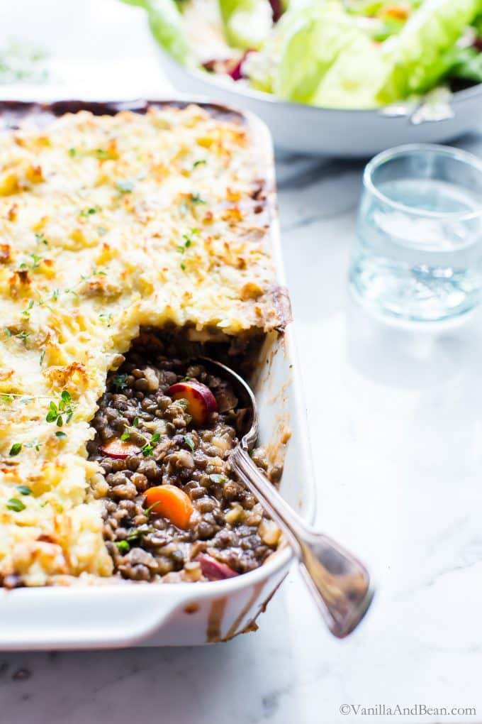 Vegetarian Cottage Pie just pulled from the oven with a spoon in the casserole dish ready to share.