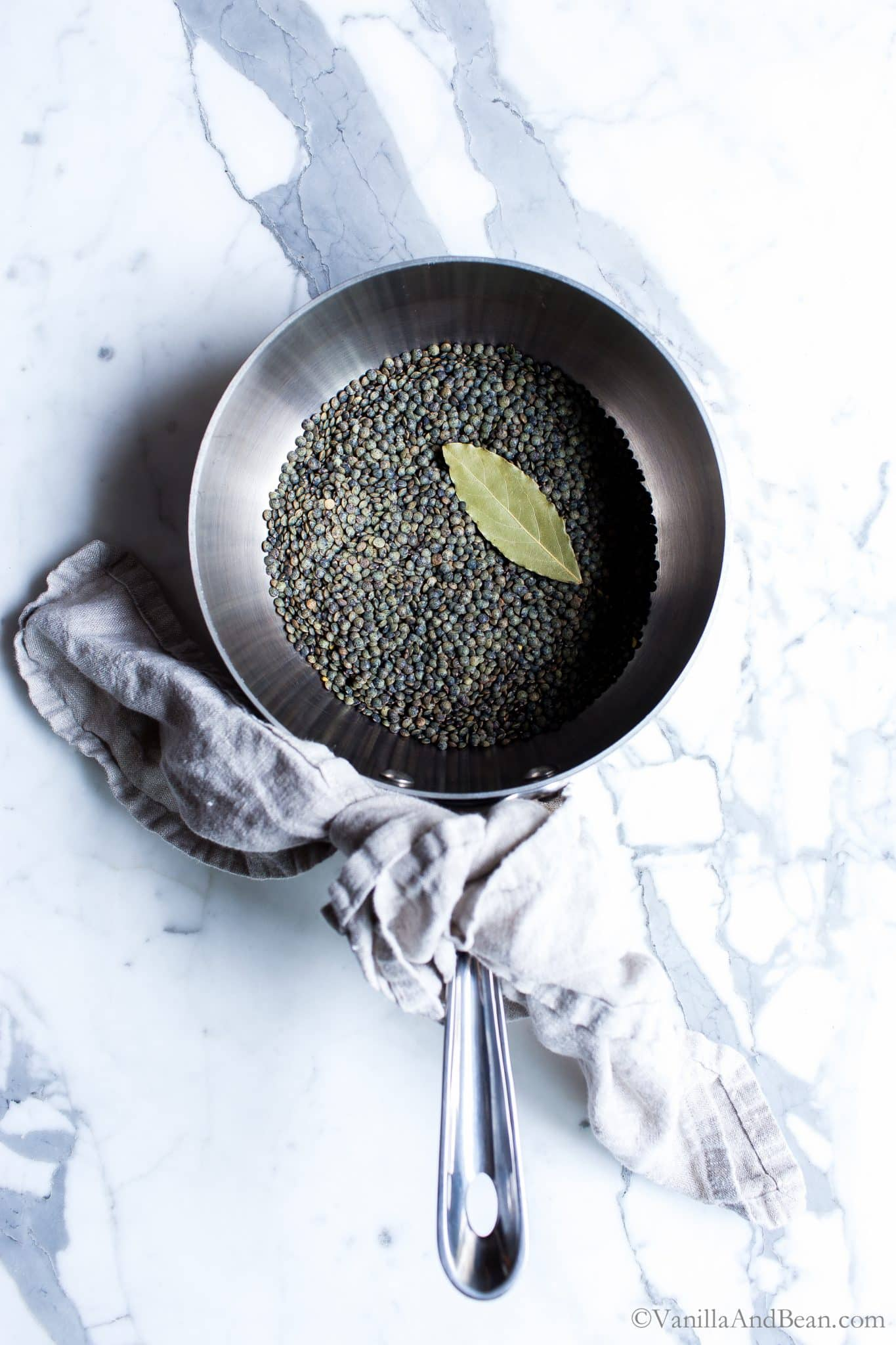 Overhead shot of French lentils in a pan with a bay leaf.