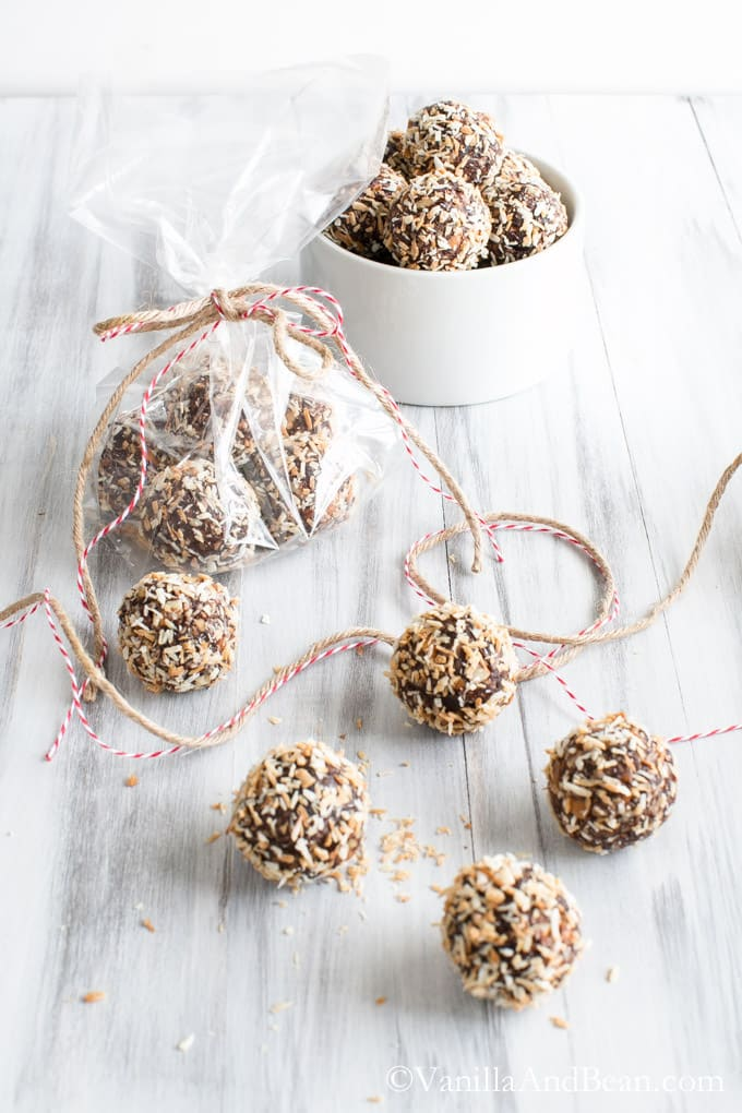 Bourbon Date Nut Truffles in a small bowl, in a clear packaging and a few pieces on a table