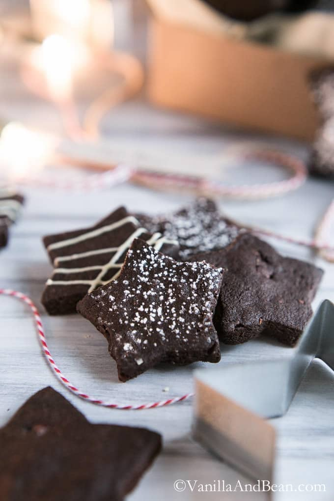 Dark Chocolate Cocoa Nib Shortbread Cookies cut into star shapes, sprinkled with powder sugar. on a white board.