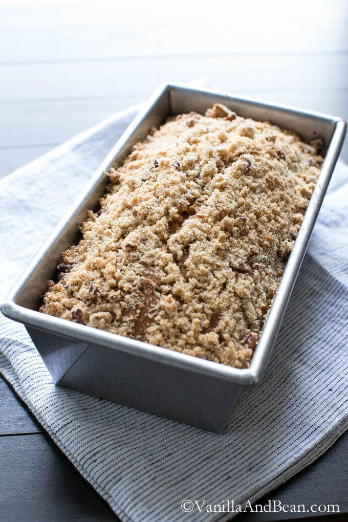 Cranberry Orange Bread with Pecans in a loaf pan topped with streusel