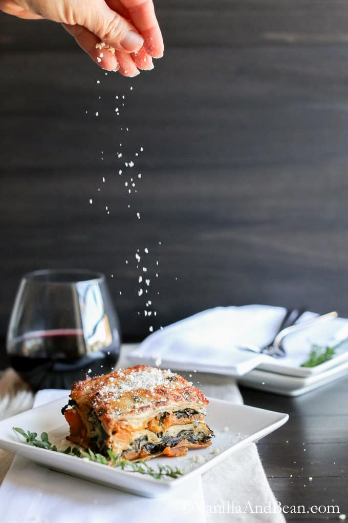 A slice of butternut squash and kale lasagna on a plate with a sprig of thyme on the side and sprinkled with Parmesan cheese. A glass of wine on one side of the plate.