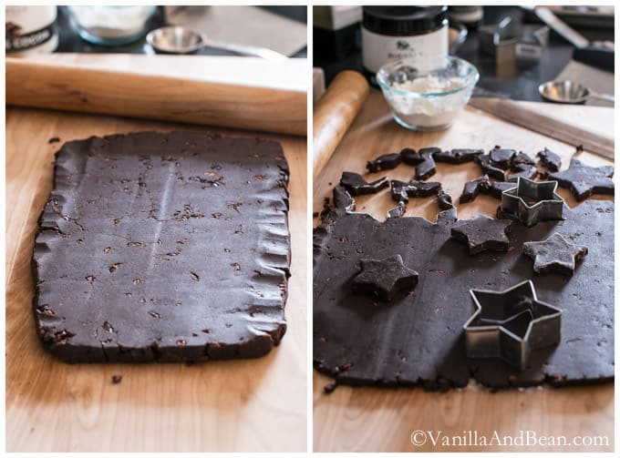 A flattened, rectangular chocolate dough on a floured surface with a rolling pin, a star-shaped cookie cutter and cut cookies