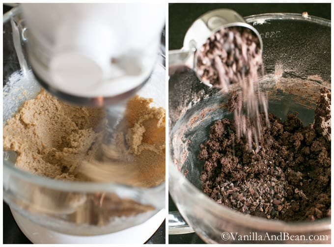 Sugar in a bowl of a stand mixer and cacao nibs in a measuring cup poured on the mixture