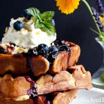 A close up of the waffles topped with blueberries, cream and syrup.