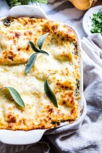 Butternut Squash Lasagna in a baking pan topped with fresh sage.