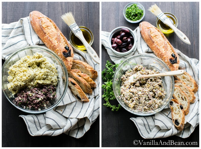 The artichoke mixture in a big glass bowl surrounded by small bowls of olives, parsley, olive oil, and a baguette with a few slices of it.