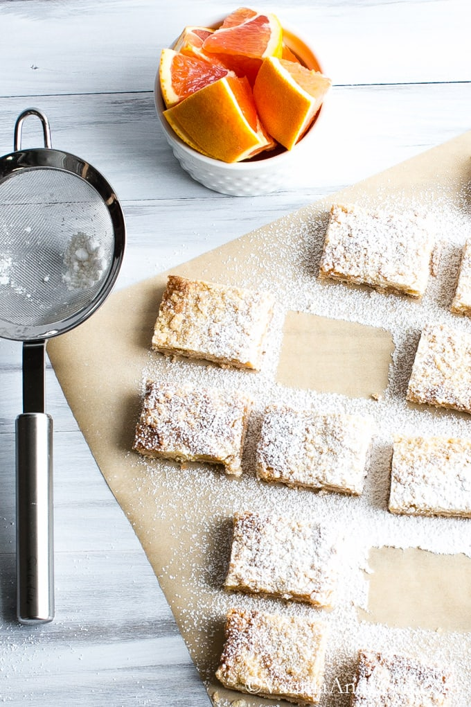 The tart cut into squares sprinkled with powdered sugar are lined up on parchment paper and a bowl of sliced oranges and a fine mesh sieve with beside it.