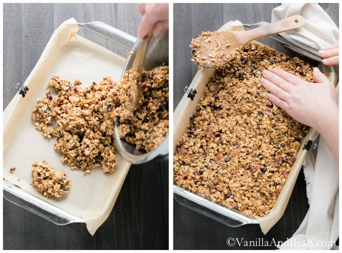 The Peanut Butter Fruit and Nut Granola mixture is poured on a baking dish with parchment paper. It is spread and pressed firmly.