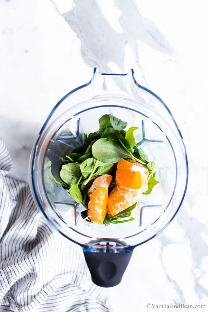 Spinach and oranges in the pitcher of a high speed blender.