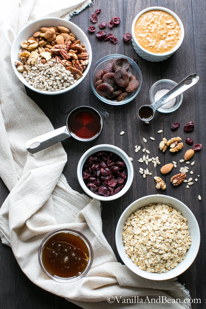 Ingredients for the Peanut Butter Fruit and Nut Granola Bars in bowls on a table
