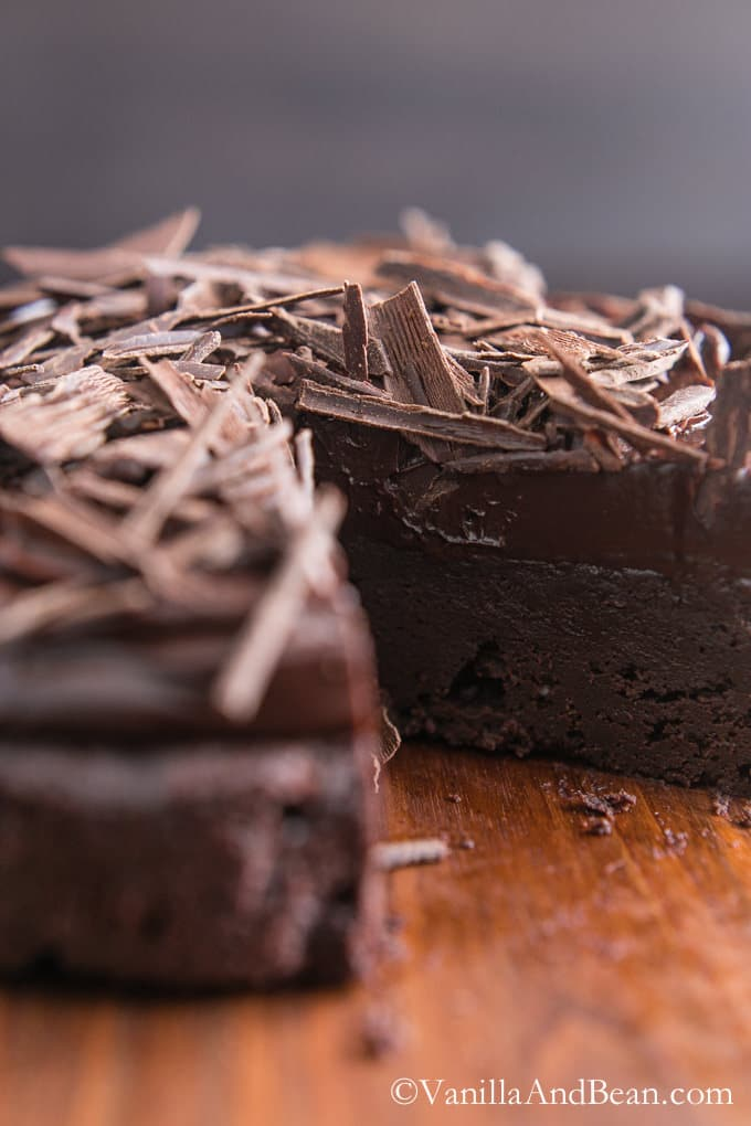 A flourless chocolate cake sprinkled with chocolate shavings and missing a slice to show the inside.