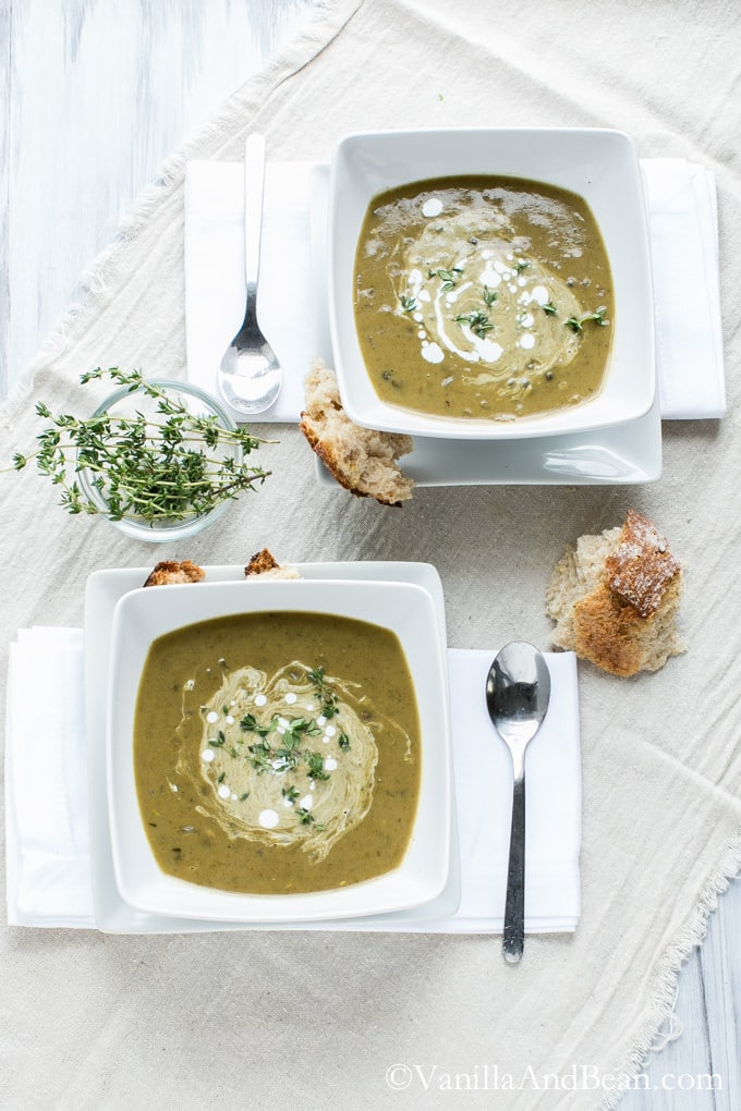 Coconut Curried French Lentil Soup in two square bowls drizzled with coconut milk and garnished with thyme. The bowls are surrounded with pieces of bread, a small bowl of dried thyme and a spoon for each bowl.