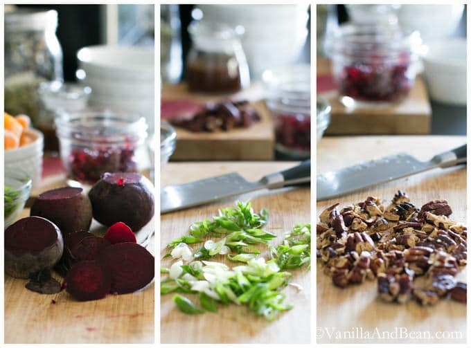 On a chopping board at a time are beets, green onions and pecans surrounded by other ingredients.