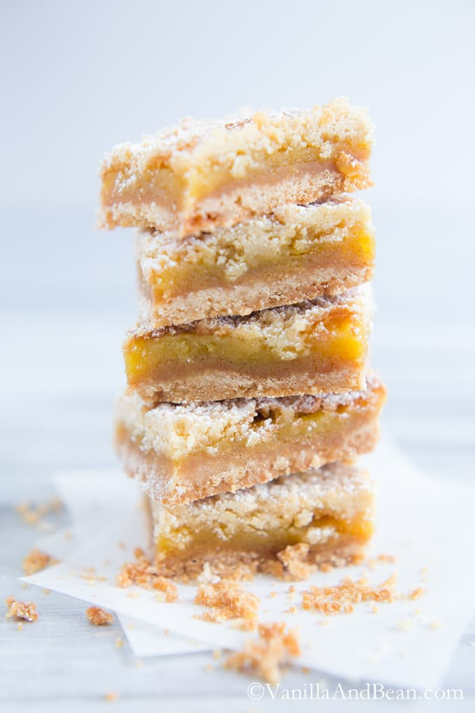 A stack of Orange Crumble Tart bars surrounded by a few crumbs.