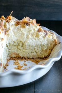 Side view of the Triple Coconut Creme Pie in a pie plate with its layers of pie, cream, and topping shown.