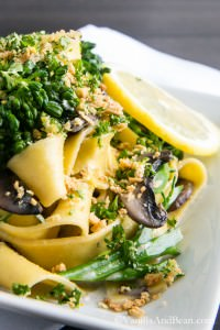 A plate of Pappardelle with Broccolini and Crunchy Gremolata and a slice of lemon.