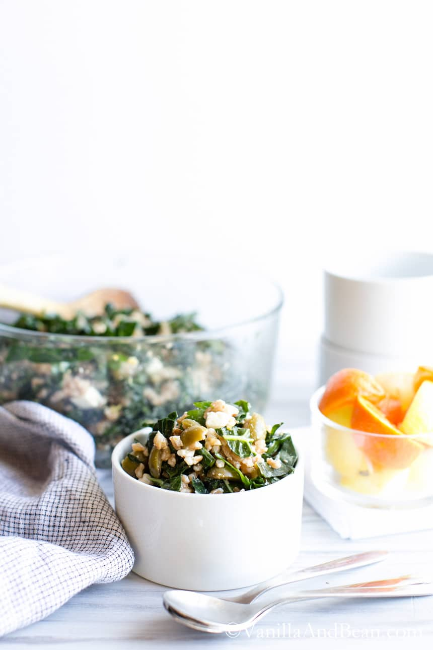 A big bowl with a wooden spoon and a small bowl of Farro, Kale and Olive Salad with Citrus Vinaigrette.