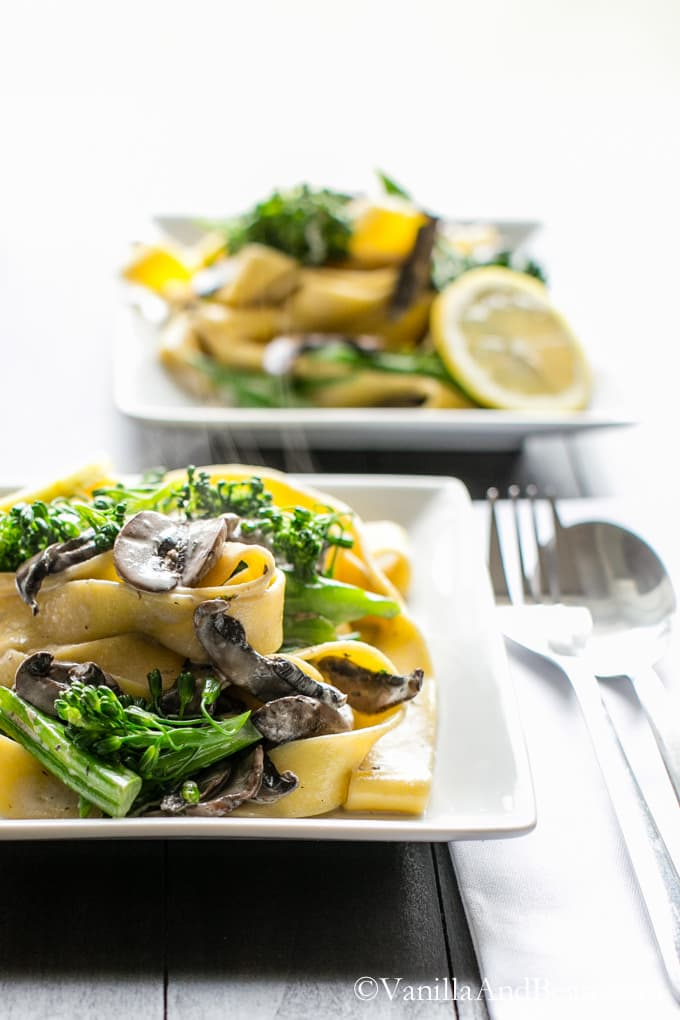 Two plates of Pappardelle with Broccolini and Crunchy Gremolata served on a table with spoon and fork and table napkin.