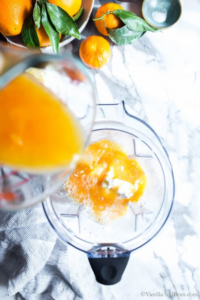 Pouring orange juice into a pitcher of a VitaMix