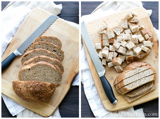 A loaf of bread sliced, cut into strips and then cubes on a chopping board with a serrated knife.