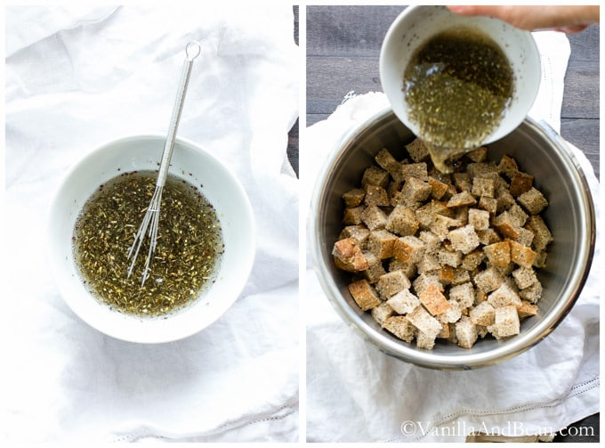 A bowl of coconut oil with seasoning and herbs poured on a stainless steel bowl containing cubed bread.