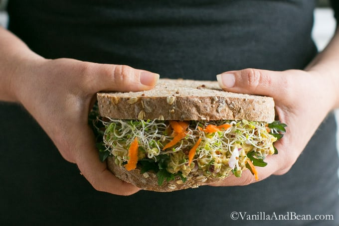 Smashed Chickpea Salad Sandwich being held with two hands