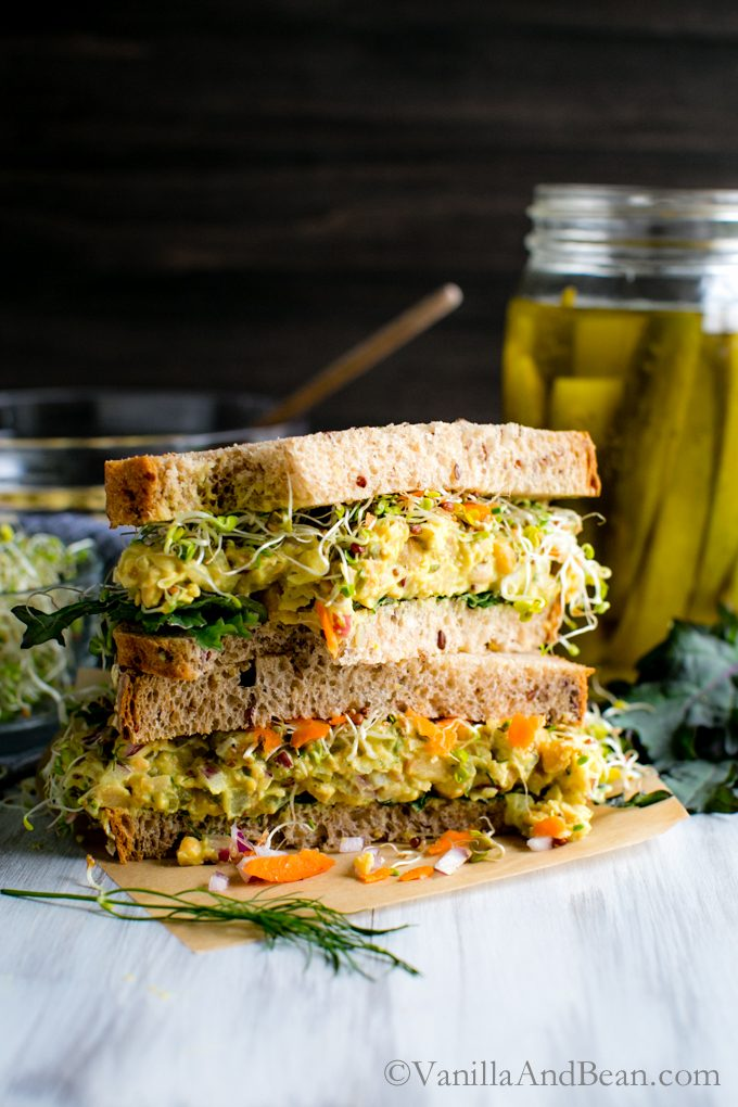 Tangy Smashed Chickpea Salad Sandwich sliced in half and stacked on top of one another. There's pickles in the background for snacking!