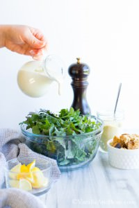 Caesar Dressing poured into a bowl of kale surrounded by a small bowl of croutons, a small bowl of lemon wedges and a glass of Parmesan mixture.