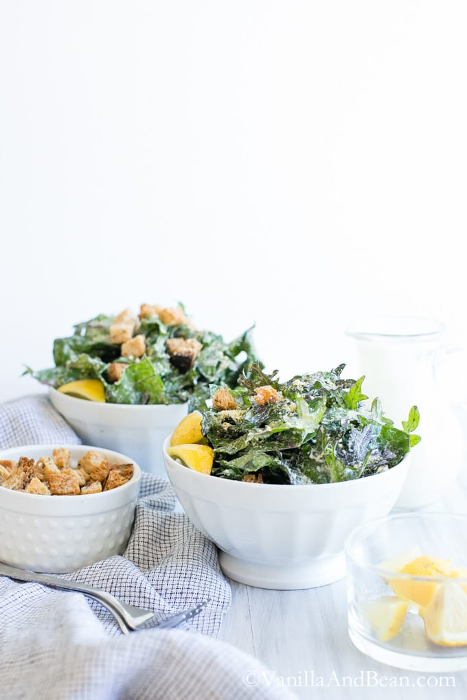 Two bowls of Vegan Caesar Dressing with Massaged Kale and Parmesan and a small bowl of croutons.