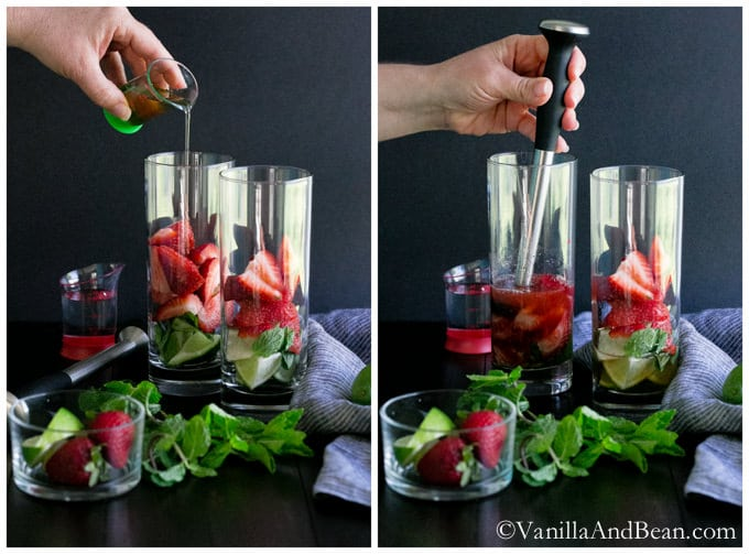 Pouring syrup into a glass of lime wedges, mint leaves and three quartered strawberries. A muddler is then used for the mixture.